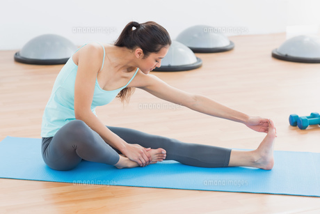 Sporty woman stretching hand to leg in fitness studioの素材 [FYI00000635]