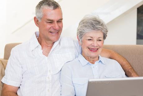 Senior couple using laptop on sofaの素材 [FYI00000638]