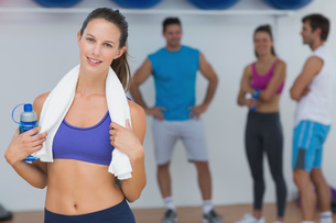 Fit female holding water bottle with fitness class in backgroundの写真素材 [FYI00000641]