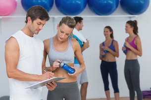 Couple looking at clipboard with fitness class in backgroundの写真素材 [FYI00000643]