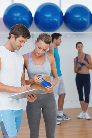 Couple looking at clipboard with fitness class in backgroundの素材 [FYI00000644]