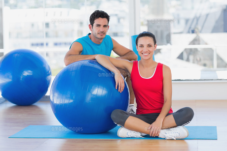 Instructor and smiling woman with exercise ball at gymの素材 [FYI00000646]