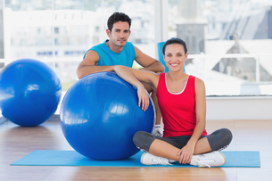 Instructor and smiling woman with exercise ball at gymの写真素材 [FYI00000646]