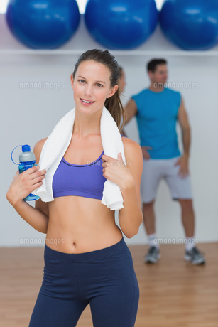 Portrait of a fit female holding water bottle with a man in background at gymの素材 [FYI00000647]