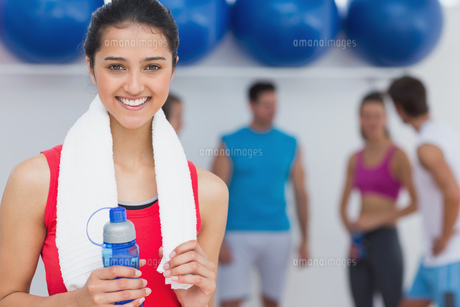 Female holding water bottle with fitness class in backgroundの写真素材 [FYI00000648]