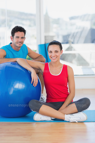 Instructor and smiling woman with exercise ball at gymの素材 [FYI00000649]