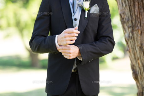 Groom adjusting sleeve in gardenの写真素材 [FYI00000652]