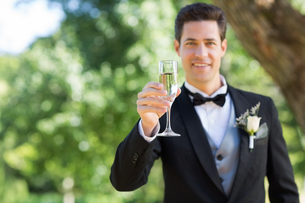 Smiling groom holding champagne flute in gardenの写真素材 [FYI00000656]