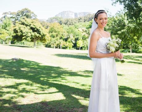 Happy bride holding flower bouquet in gardenの素材 [FYI00000661]