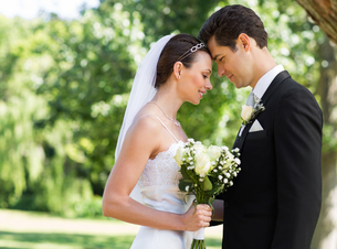 Newly wed couple with head to head in gardenの写真素材 [FYI00000662]