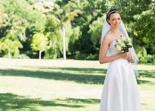 Attractive bride holding flowers in parkの写真素材 [FYI00000663]