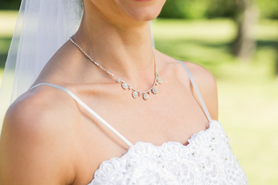 Closeup of bride wearing necklace in gardenの写真素材 [FYI00000667]