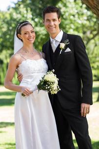 Newly wed couple standing in gardenの写真素材 [FYI00000668]