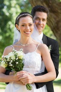 Groom embracing bride from behind in gardenの写真素材 [FYI00000672]