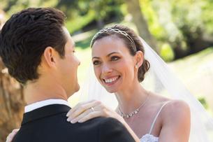 Bride looking at groom in gardenの写真素材 [FYI00000680]