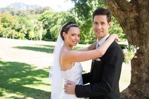 Smiling bride and groom embracing in gardenの写真素材 [FYI00000681]