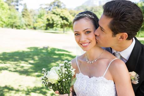 Groom kissing beautiful bride on cheek in gardenの素材 [FYI00000682]
