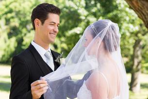 Groom unveiling his bride in gardenの写真素材 [FYI00000685]