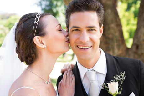 Bride kissing groom on cheek in gardenの素材 [FYI00000689]