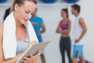 Trainer writing on clipboard with fitness class in background at gymの写真素材 [FYI00000690]