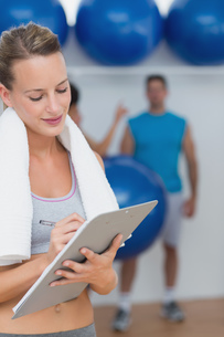 Trainer writing on clipboard with fitness class in background at gymの写真素材 [FYI00000691]