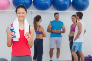 Female holding water bottle with fitness class in backgroundの写真素材 [FYI00000692]