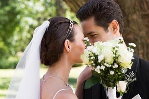 Couple kissing behind flowers in gardenの写真素材 [FYI00000694]