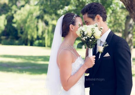 Couple kissing behind bouquet in gardenの写真素材 [FYI00000696]