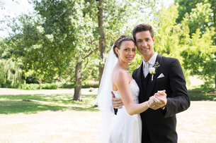 Loving newly wed couple dancing in gardenの写真素材 [FYI00000698]
