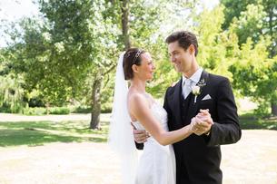 Loving bride and groom dancing in gardenの写真素材 [FYI00000699]