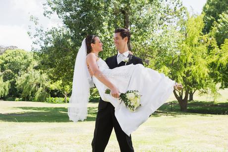 Groom carrying bride in arms at gardenの写真素材 [FYI00000700]