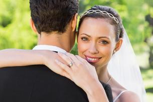Beautiful bride embracing groom in gardenの写真素材 [FYI00000701]