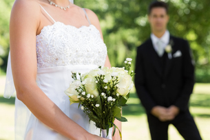 Bride holding bouquet with groom in backgroundの写真素材 [FYI00000702]