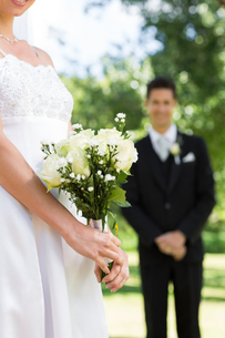 Bride holding bouquet with groom standing in backgroundの写真素材 [FYI00000703]