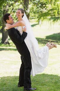 Side view groom lifting bride in gardenの写真素材 [FYI00000704]