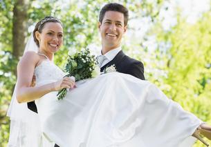 Groom carrying bride in gardenの写真素材 [FYI00000706]