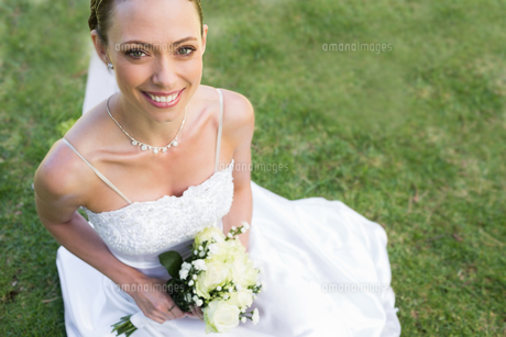 Bride holding flower bouquet while sitting in gardenの写真素材 [FYI00000707]