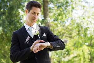 Smart groom checking time in gardenの写真素材 [FYI00000708]