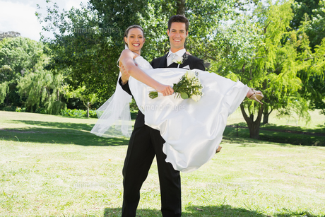 Young groom lifting bride in arms at gardenの写真素材 [FYI00000709]