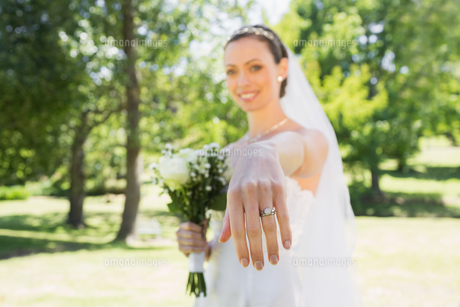 Beautiful bride showing wedding ring in gardenの素材 [FYI00000712]