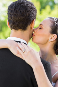 Closeup of bride kissing groom on cheekの写真素材 [FYI00000713]