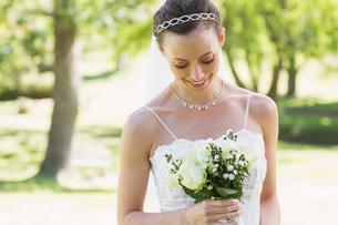 Bride looking at bouquet in gardenの写真素材 [FYI00000714]