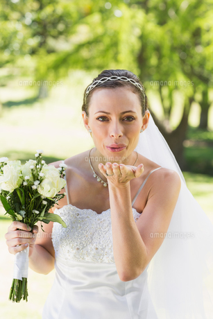 Bride with bouquet blowing kiss in gardenの素材 [FYI00000716]