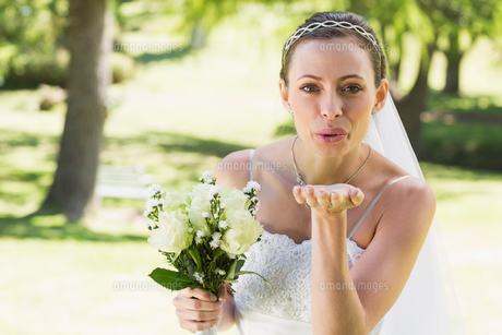 Beautiful bride with bouquet blowing kiss in gardenの素材 [FYI00000719]