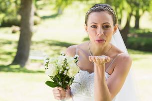 Beautiful bride with bouquet blowing kiss in gardenの写真素材 [FYI00000719]