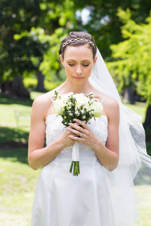 Bride holding flower bouquet in gardenの写真素材 [FYI00000723]