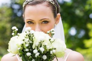 Bride peeking over bouquet in gardenの写真素材 [FYI00000725]
