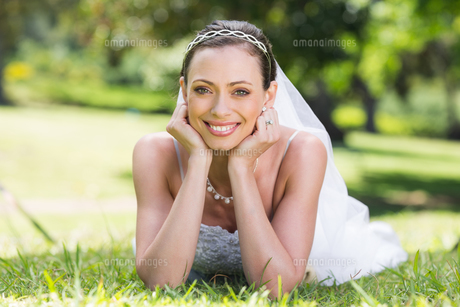 Bride in wedding gown lying on grassの素材 [FYI00000727]