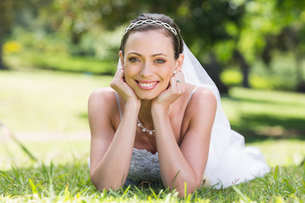 Bride in wedding gown lying on grassの写真素材 [FYI00000727]