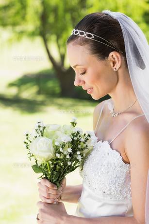 Shy bride holding bouquet in gardenの写真素材 [FYI00000729]